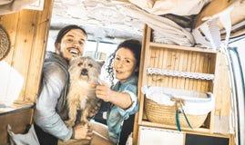 Modniś para z śliczny psi podróżować wpólnie na oldtimer furgonetce Zdjęcia Stock
