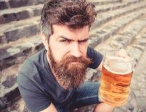 Modniś pije piwny plenerowego na surowej twarzy, podnoszący napój up Rozwesela pojęcie Mężczyzna z brodą i wąsy trzyma szkło obraz stock