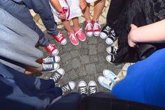 Modniś pozycja z sneakers w okręgu na beton ziemi Odgórny widok chłodno młodości białego, czarnego, czerwieni i menchii gym butów Zdjęcie Royalty Free