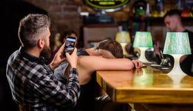Modniś robi zabawie opiły przyjaciel Mężczyzna pijący spada uśpiony i facecie z smartphone Modniś bierze fotografia pijącego przy obraz stock