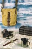 Modniś torba, niektóre rezerwuje, wristwatch i stara ekranowa kamera, Herbata w metalu kubku wielka mapa obraz stock