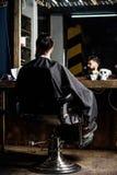 Modniś z brodą czeka fryzjera męskiego i ostrzyżenia Mężczyzna z brodą zakrywającą z czarnym przylądkiem siedzi w fryzjera krześl obraz stock