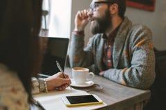 Modniś z brodą z smartphone i laptopem na stole daje wewnątrz obraz stock