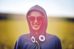 Modniś dziewczyna w hoodie, okularach przeciwsłonecznych i hełmofonach w plenerowym, Zdjęcia Stock