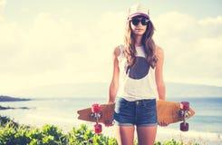 Modniś dziewczyna z łyżwa deskowymi jest ubranym okularami przeciwsłonecznymi Obrazy Stock
