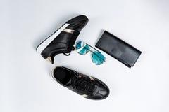 Modni sneakers na bia?ej podeszwie z, okularach przeciws?onecznych z b??kitnymi szk?ami i czarnej kiesie na bielu czarnymi skarpe zdjęcia stock