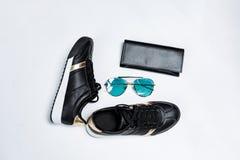 Modni sneakers na bia?ej podeszwie z, okularach przeciws?onecznych z b??kitnymi szk?ami i czarnej kiesie na bielu czarnymi skarpe zdjęcie stock