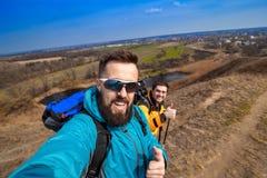 Modnisiów młodzi przyjaciele bierze selfie na wzgórzu w kampanii, c Fotografia Stock