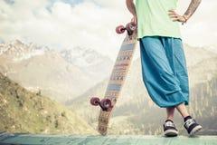 Modnisiów potomstwa i przystojny mężczyzna z longboard jeździć na deskorolce przy górą Fotografia Stock