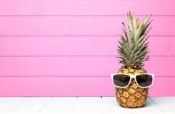 Modnisia ananas z okularami przeciwsłonecznymi przeciw różowemu drewnu zdjęcie stock
