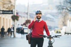 Modnisia biznesmena dojeżdżający z bicyklem i smartphone na sposobie pracować w mieście fotografia royalty free