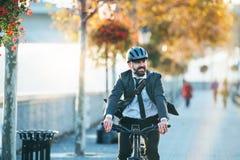 Modnisia biznesmena dojeżdżający z elektrycznym rowerowym podróżować domem od pracy w mieście fotografia stock