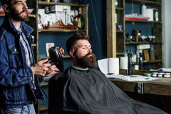 Modnisia brodaty klient dostać fryzurę Fryzjer męski z hairdryer dmucha z włosy z przylądka Zakładu fryzjerskiego pojęcie Fryzjer Obrazy Stock