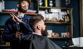 Modnisia brodaty klient dostaje fryzurę Fryzjer męski na rozochoconej twarzy z hairdryer tytułowania włosy klient Fryzjer męski z Obraz Stock