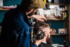 Modnisia brodaty klient dostaje fryzurę Fryzjer męski z hairdryer osuszką i tytułowanie włosy klient Fryzjer męski z hairdryer Fotografia Royalty Free