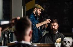Modnisia brodaty klient dostaje fryzurę Fryzjer męski z hairdryer pracuje na fryzurze dla brodatego mężczyzna, zakład fryzjerski Obraz Stock