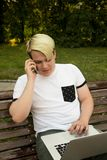 Modnisia facet dzwoni przez telefonu komórkowego i czytelniczej informaci od netbook zdjęcie royalty free