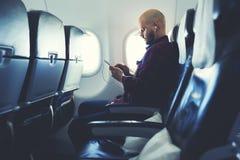 Modnisia facet ogląda wideo na komórka telefonie, podczas gdy siedzi w samolocie Fotografia Royalty Free