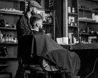 Modnisia klient dostać nowego ostrzyżenie Fryzjer męski z brodatym mężczyzna patrzeje lustro, zakładu fryzjerskiego tło Ostrzyżen zdjęcia royalty free