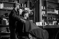 Modnisia klient dostać nowego ostrzyżenie Fryzjer męski z brodatym mężczyzna patrzeje lustro, zakładu fryzjerskiego tło Ostrzyżen zdjęcie royalty free