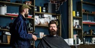Modnisia klient dostać nowego ostrzyżenie Fryzjer męski z włosianym cążki patrzeje lustro, zakładu fryzjerskiego tło Fryzjer męsk Fotografia Royalty Free