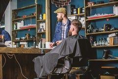 Modnisia klient dostać nowego ostrzyżenie Fryzjera męskiego skończony żyłować Fryzjer męski z brodatym mężczyzna patrzeje lustro, fotografia stock