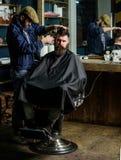 Modnisia klient dostaje ostrzyżenie Fryzjer męski z cążki arymażu włosy na świątyni klient Modnisia stylu życia pojęcie barber Zdjęcie Royalty Free