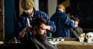 Modnisia klient dostaje ostrzyżenie Fryzjera męskiego tytułowania włosy brodaty klient z gręplą i cążki Ostrzyżenia pojęcie barbe fotografia royalty free