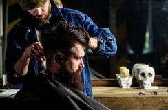 Modnisia klient dostaje ostrzyżenie Fryzjera męskiego tytułowania włosy brutalny brodaty klient z cążki Ostrzyżenia pojęcie Fryzj obraz stock