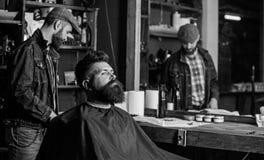 Modnisia klient dostaje ostrzyżenie Mężczyzna z brodą zakrywającą z czarnym przylądka czekaniem podczas gdy fryzjera męskiego odm zdjęcia royalty free
