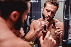 Modnisia mężczyzna mienia butelka w łazience Zdjęcie Stock