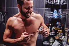 Modnisia mężczyzna seansu butelka w łazience Zdjęcie Stock
