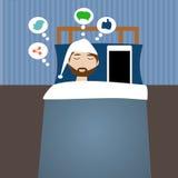 Modnisia mężczyzna w łóżkowym czasie z mądrze telefonem Fotografia Royalty Free