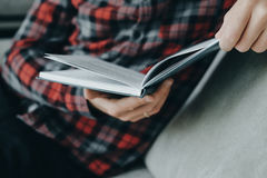 Modnisia mężczyzna w czerwonej w kratkę koszulowej czytelniczej książce i kłamstwach na Fotografia Stock