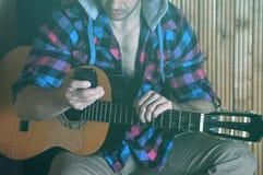 Modnisia mężczyzna wręcza chwyta telefon i starą krekingową gitarę Zdjęcie Royalty Free