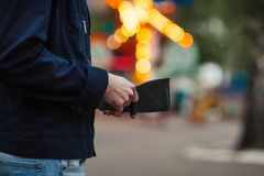 Modnisia mężczyzna wręcza mienie portfel z kredytowymi kartami i stertą pieniądze Obrazy Stock