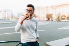 Modnisia mężczyzny pozycja z takeaway kawą chodzi na th miasta ulicie, ono uśmiecha się plesantly, Szczęśliwy beztroski przystojn fotografia royalty free