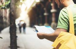 Modnisia młody człowiek patrzeje mapę i trzyma z plecakiem Mówić widoku podróżnika planowania turystyczna trasa na tła słońca mie zdjęcia royalty free