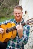 Modnisia mężczyzna z czerwoną brodą bawić się gitarę Obrazy Royalty Free