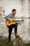 Modnisia mężczyzna z czerwoną brodą bawić się gitarę Obraz Stock