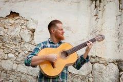Modnisia mężczyzna z czerwoną brodą bawić się gitarę Obrazy Stock