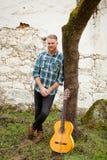 Modnisia mężczyzna z czerwoną brodą z gitarą Fotografia Royalty Free