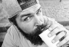 Modnisia napoju kawa iść podczas gdy siedzi schodki outdoors Miastowy karmowy kultury pojęcie Smakowity łyczka pojęcie Smakowita  zdjęcia stock