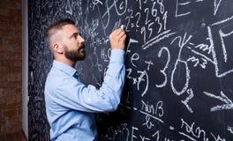 Modnisia nauczyciela writing na dużym blackboard z matematycznie symb Fotografia Stock