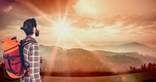 Modnisia przewożenia plecak z kamerą i patrzeć góry podczas gdy stojący na trawiastych śródpolnych agains Zdjęcia Royalty Free