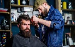 Modnisia stylu życia pojęcie Fryzjer męski z cążki arymażu włosy na świątyni klient Modnisia klient dostaje ostrzyżenie barber Obraz Royalty Free