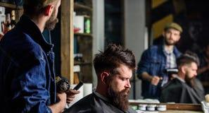 Modnisia stylu życia pojęcie Fryzjer męski z hairdryer pracuje na fryzurze dla brodatego mężczyzna zakładu fryzjerskiego tła modn Obrazy Royalty Free
