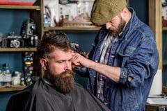 Modnisia stylu życia pojęcie Modnisia klient dostaje ostrzyżenie Fryzjer męski z włosianego cążki pracą na fryzurze dla brodatego Obrazy Stock