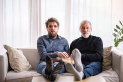 Modnisia syn i jego starszy ojciec z laptopem w domu Zdjęcie Stock