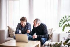 Modnisia syn i jego starszy ojciec z laptopem w domu Obraz Stock
